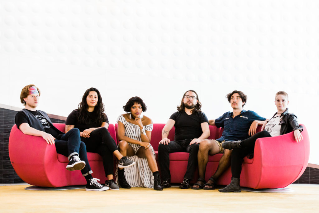 the original band lineup a group of six people of varying genders and races mostly dressed in black sit comfortably on a red couch