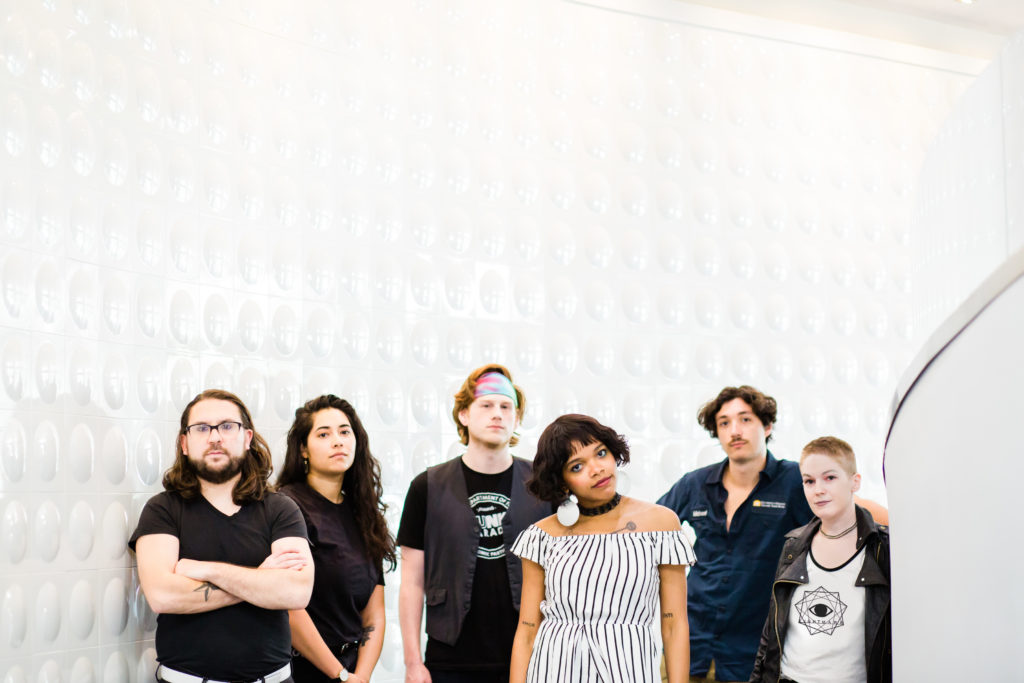 six original band members of various genders and races stand seriously against a textured white wall