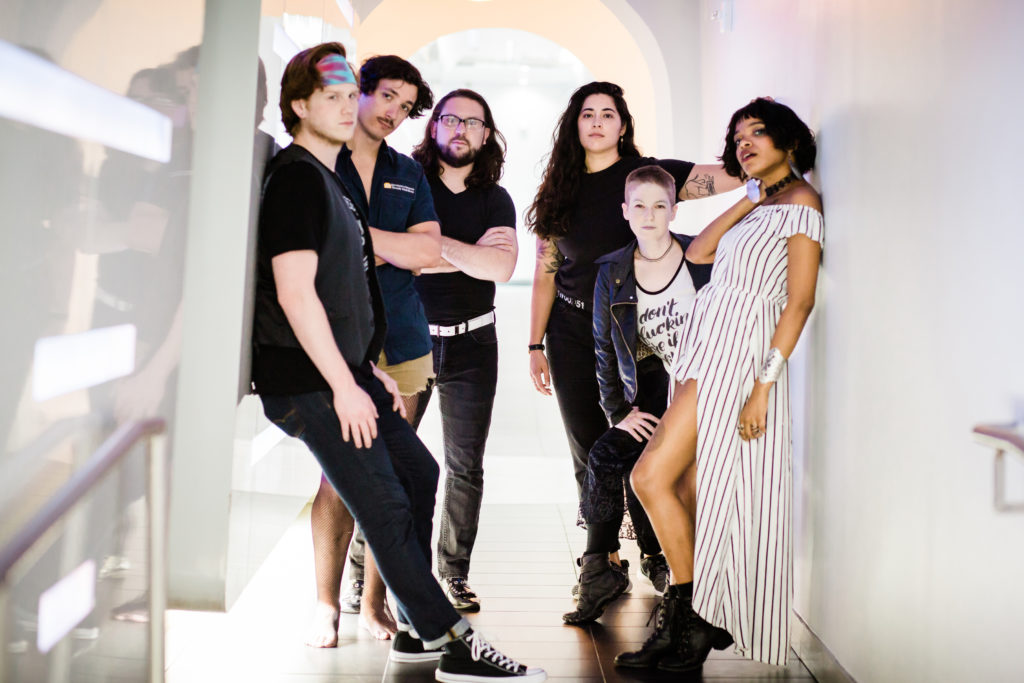 six original band members of various genders and races pose seriously in a white hallway