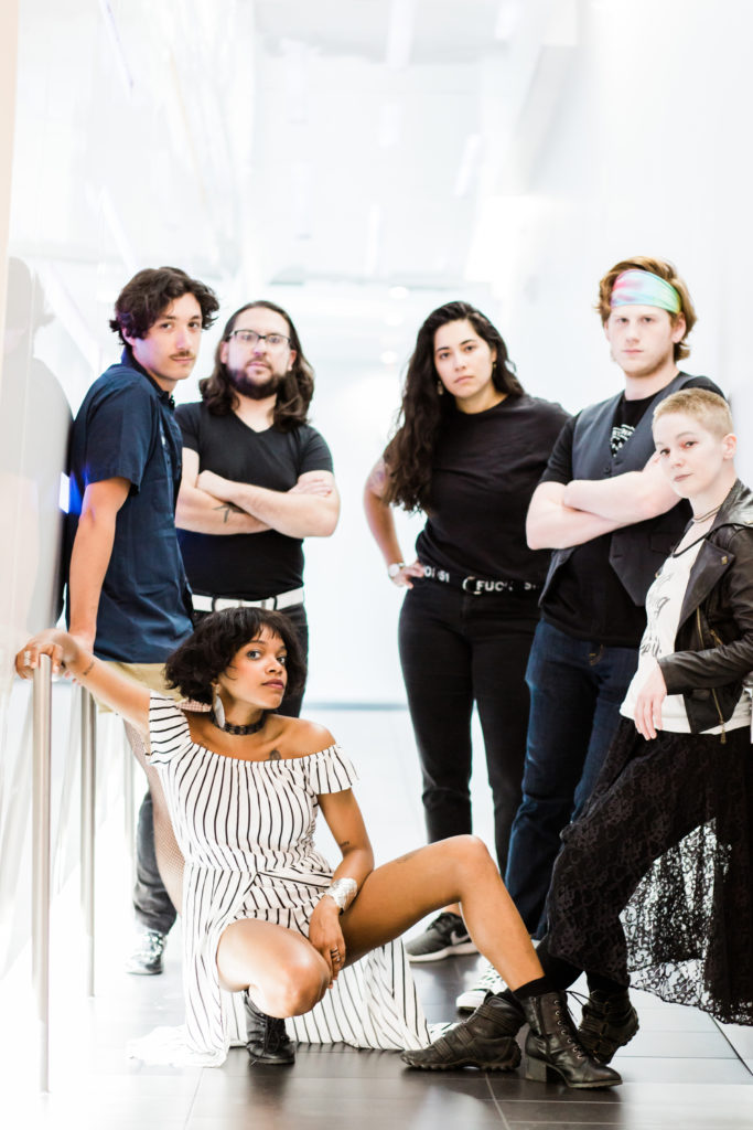 six original band members of various genders and races post seriously in a very brightly lit white hallway