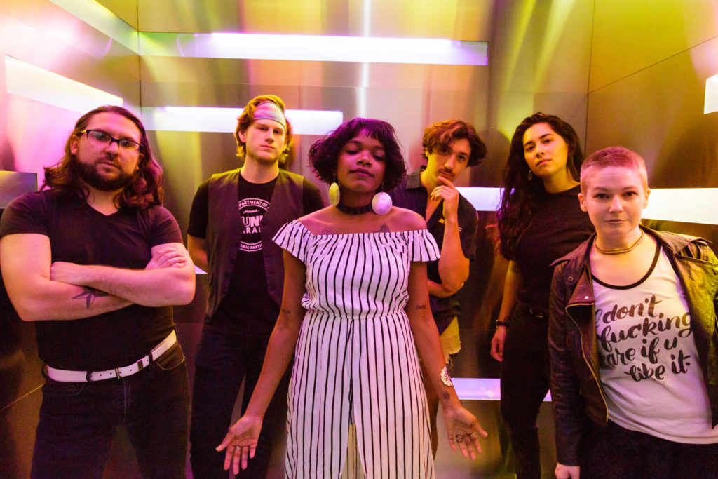 six band members of varying genders and races pose serenely in a small chrome room with multicolored soft warm light