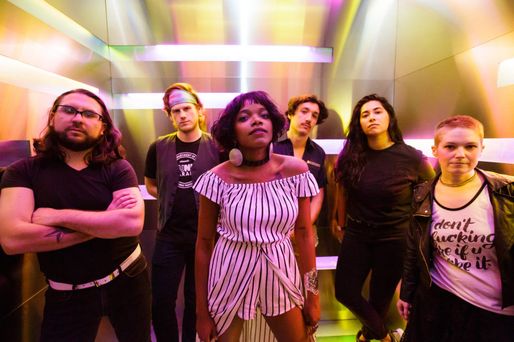 six original band members pose with a little attitude in a small chrome room with multicolored soft warm light