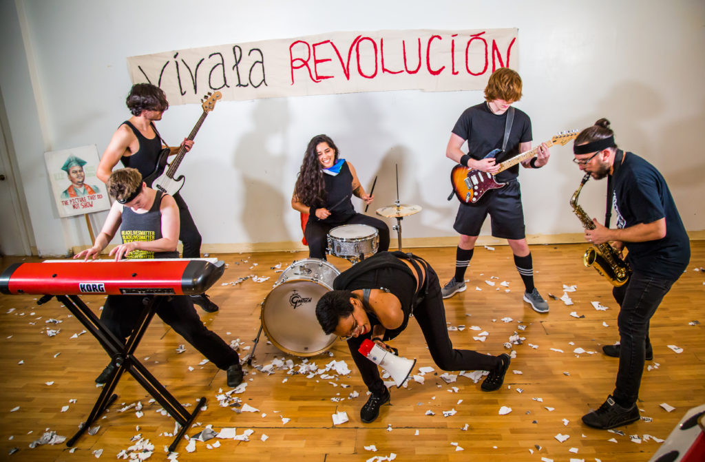 """a still from a music video shoot, the band poses with instruments and a bullhorn rocking out hard. a banner on the back wall reads """"viva la revolicion"""""""
