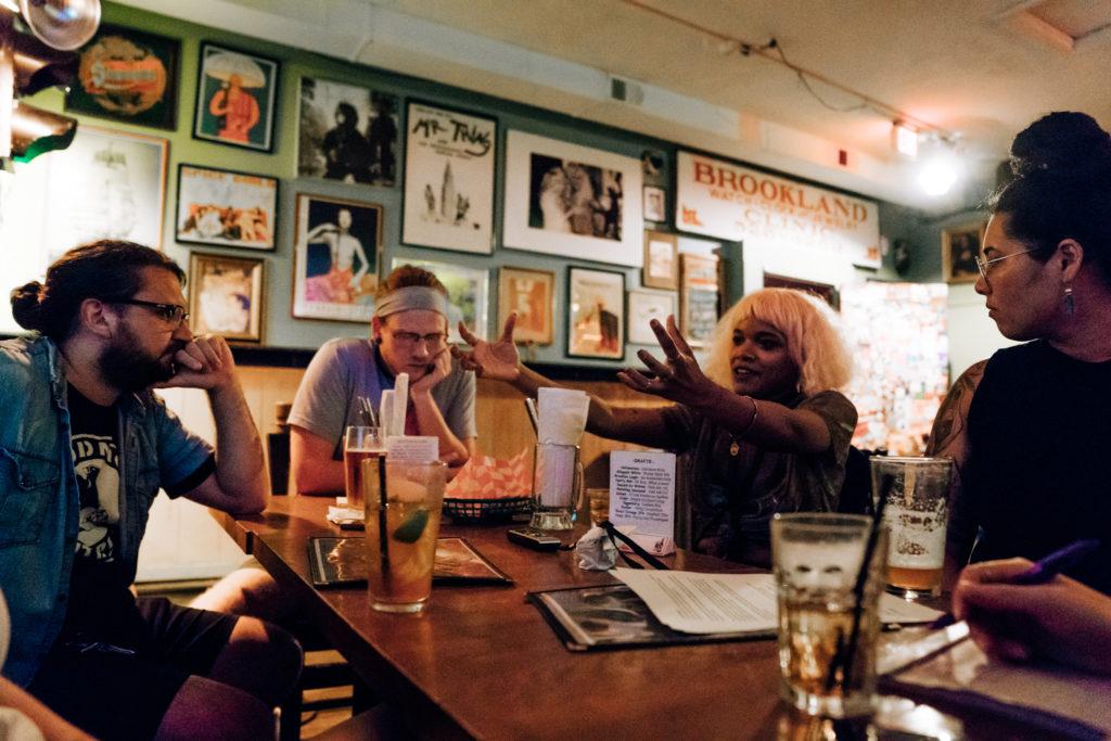the band chats at a bar table