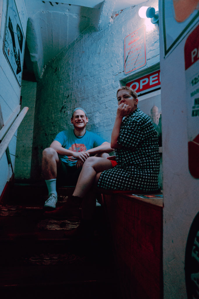 Vitamin Dee and Beck sit looking thoughtful in a stairwell with bluish light