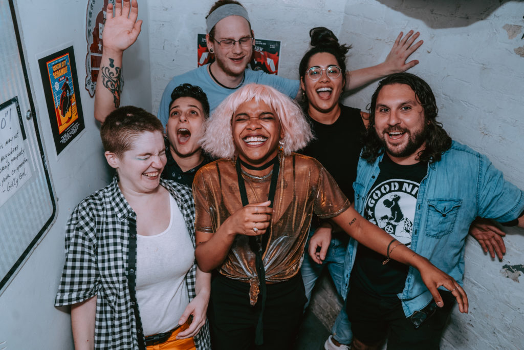 The band laughs with full joy in a candid moment in a stairwell