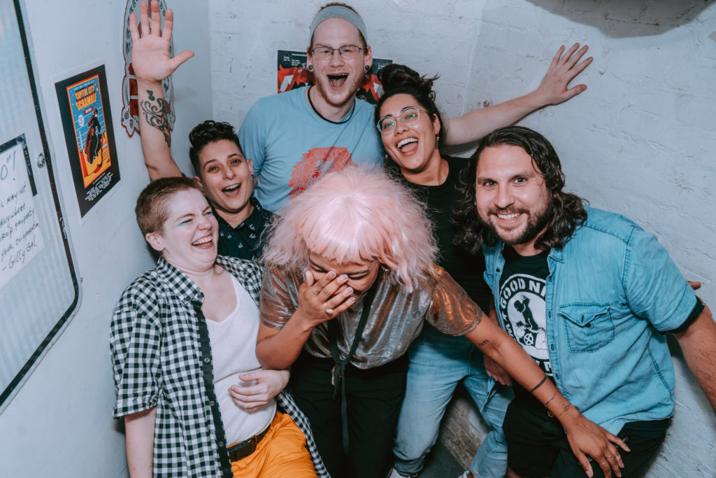 The band laughs with full joy, almost falling over in a candid moment in a stairwell