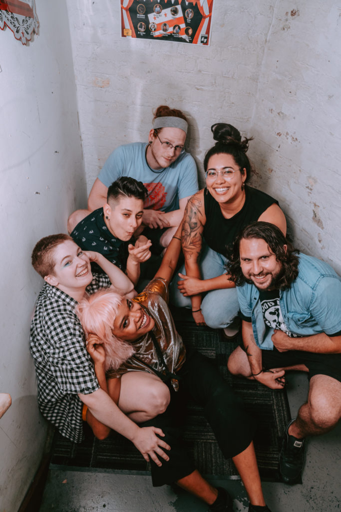 the band all piles affectionately in a stairwell