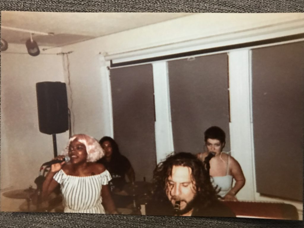 a grainy disposable camera photo of the band mid-performance, everyone is sweaty and energetic