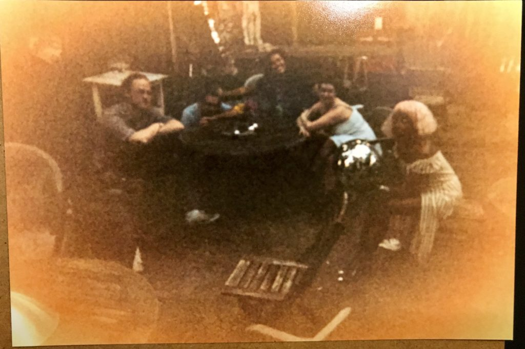 a grainy, washed out photo of Lightmare seated at various garden tables outdoors