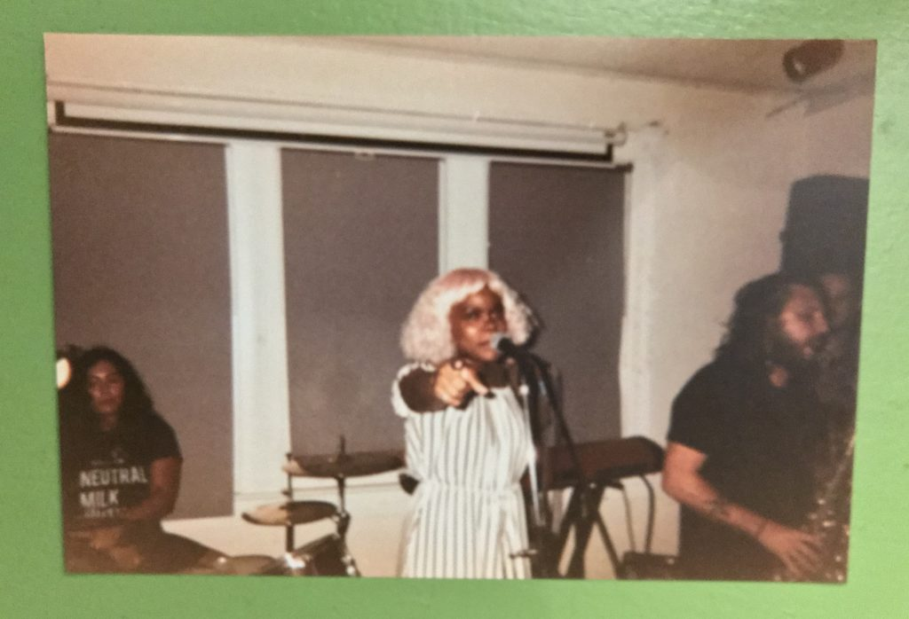 a disposable camera photo of Shady singing at Rhizome, pointing towards the camera forcefully