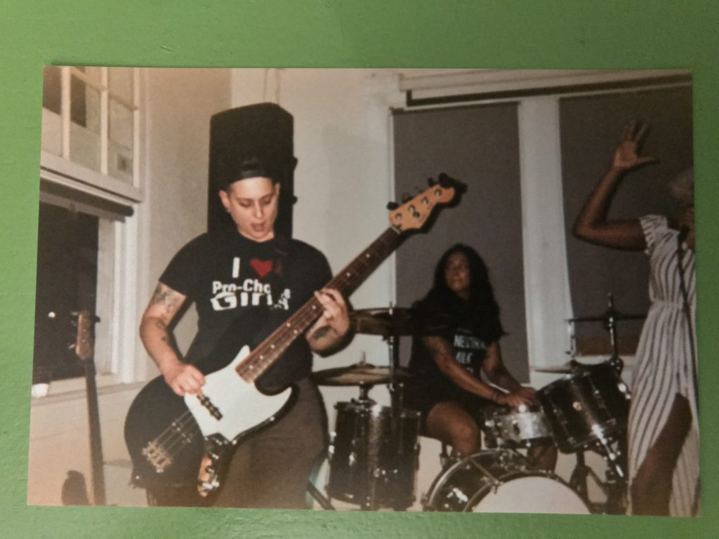 grainy disposable camera photo of Frankie playing the bass with a funky facial expression. Josette plays a sparkly drum kit in the background
